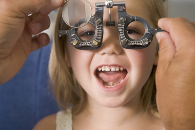 Optometrist in exam room with young girl in chair smiling